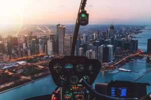 A cityscape at twilight, from the perspective of a pilot in the cockpit of a helicopter.