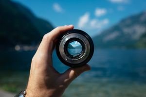 a picture of a camera lens being held by a hand. The lens is detached from a camera, and focussing a picture of a lake and tree-lined mountains. The rest of the lake, sky (which is blue with minimal white clouds), and mountains are out of focus.