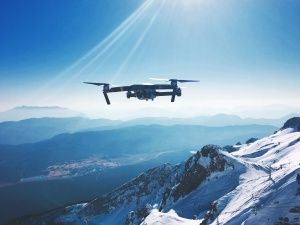 A quadracopter / drone with a camera hovering at high altitude above a snowy mountain. A city can be seen in the distance, some climbers are traversing up a climbing route, and only a solar flare affects the tone of the clear sky.
